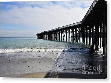 Canvas Print featuring the photograph Evening Pier Shadows Are Lost In The Surf by Debby Pueschel