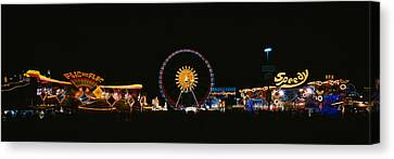 Ferris Wheel And Neon Signs Lit Canvas Print by Panoramic Images