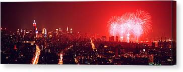Fireworks Display At Night Over A City Canvas Print by Panoramic Images