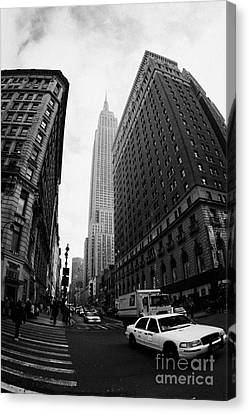 Fisheye Shot Of Yellow Cab And Empire State Building At Intersection Of 34th Street Broadway 6th Canvas Print by Joe Fox