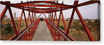 Footbridge With A City Canvas Print by Panoramic Images