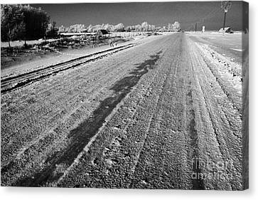 frozen salt and grit covered rural small road in Forget Saskatchewan Canada Canvas Print by Joe Fox