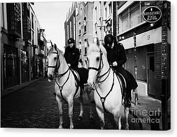 Garda Siochana Mounted Police On Horseback Taking Notes In Temple Bar Dublin Republic Of Ireland Canvas Print by Joe Fox