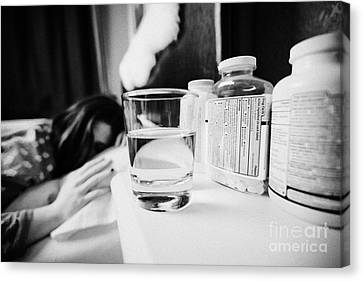 Glass Of Water And Bottles Of Pills On Bedside Table Of Early Twenties Woman In Bed In A Bedroom Canvas Print by Joe Fox