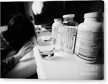 Glass Of Water And Bottles Of Pills On Bedside Table Of Early Twenties Woman Waking In Bed In A Bedr Canvas Print by Joe Fox