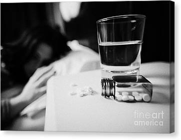 Glass Of Water And Bottles Of Sleeping Pills On Bedside Table Of Early Twenties Woman In Bed In A Be Canvas Print by Joe Fox
