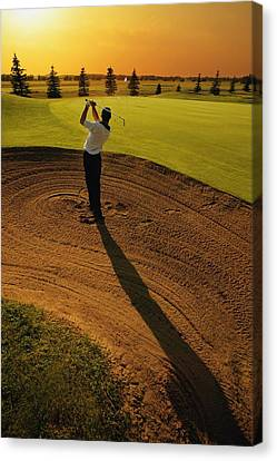 Golf Ball Canvas Print - Golfer Taking A Swing From A Golf Bunker by Darren Greenwood