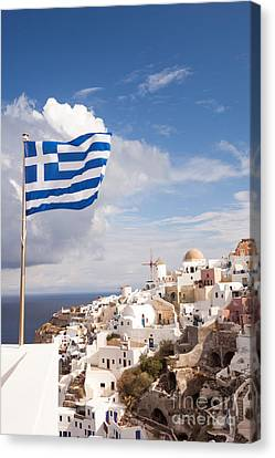 Greek Flag Waving On Oia - Santorini - Greece Canvas Print by Matteo Colombo