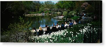 Group Of People Sitting On Benches Canvas Print