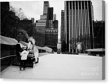 ice clearer and assistants clearing the ice at Bryant Park ice skating rink new york Canvas Print by Joe Fox