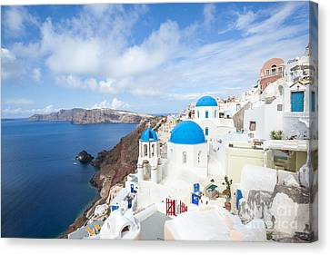 Iconic Blue Domed Churches In Oia Santorini Greece Canvas Print by Matteo Colombo