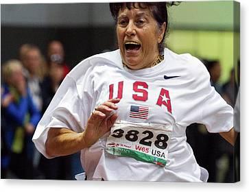 Joyful Older Female Athlete Running Canvas Print by Alex Rotas