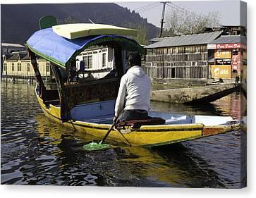 Kashmiri Man Driving This Shikara In The Still Waters Of The Dal Lake Canvas Print by Ashish Agarwal