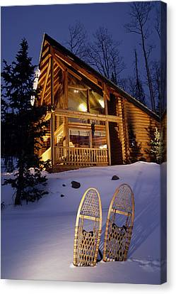 Lighted Cabin With Snowshoes In Front Canvas Print by Michael DeYoung
