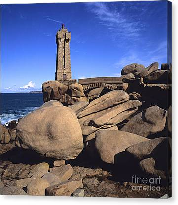 Lighthouse On Rocky Seashore. Brittany. France Canvas Print by Bernard Jaubert