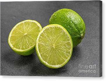 Limes On A Slate Plate Canvas Print by Palatia Photo
