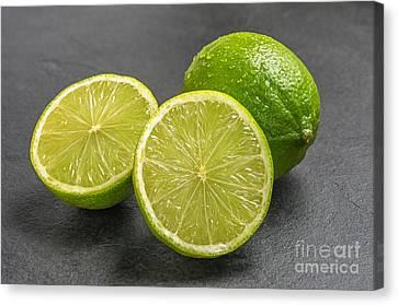 Limes On A Slate Plate Canvas Print by Palatia Photo