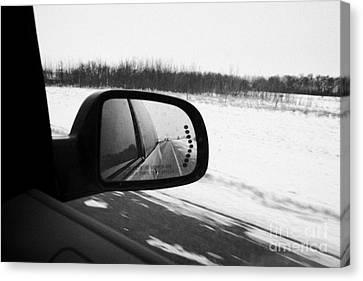 looking at side view mirror winter driving along Saskatchewan highway 11 from Saskatoon to Regina Ca Canvas Print
