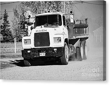 Localities Canvas Print - mack truck driving down rough unpaved rural road in farming community Saskatchewan Canada by Joe Fox