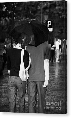 Sharing Canvas Print - Male And Female Couple Sharing An Umbrella Walking Arm In Arm Down A Wet Cobblestone Street In The Rain Krakow by Joe Fox