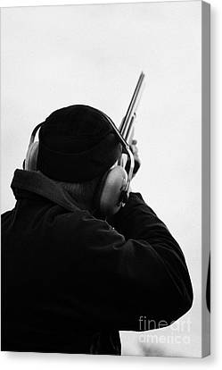 Man In Cap And Ear Defenders Takes Aim Into Sky With Shotgun On December Shooting Day Canvas Print