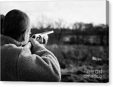 Man In Fleece Jacket Firing Shotgun Into Field With Cartridge Ejecting On December Shooting Day Canvas Print