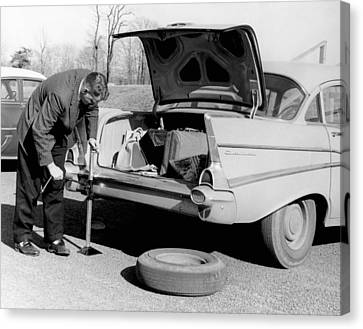 Man Jacking Up A Car Canvas Print by Underwood Archives