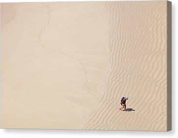 Man Leaving Footprints On Beach Canvas Print by Ashley Cooper