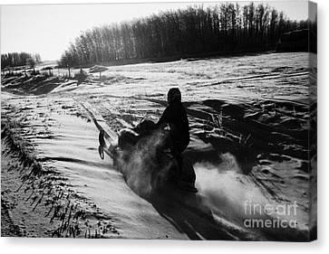 man on snowmobile crossing frozen fields in rural Forget canada Canvas Print by Joe Fox