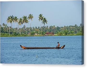 Canoe Canvas Print - Man Rowing A Long Wooden Canoe by Ali Kabas