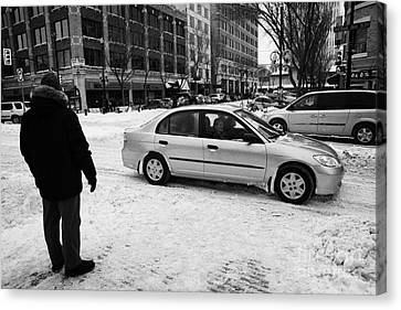 Crosswalk Canvas Print - man watching car travelling along snow covered city streets in Saskatoon Saskatchewan Canada by Joe Fox