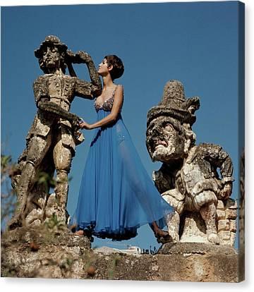 Model Standing Between Statues At The Villa Canvas Print