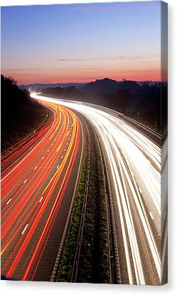 Motorway At Dusk, Gloucestershire, Uk Canvas Print by Peter Adams