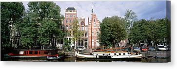 Netherlands, Amsterdam, Boats In Canal Canvas Print by Panoramic Images