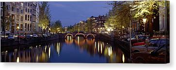 Night View Along Canal Amsterdam The Canvas Print by Panoramic Images