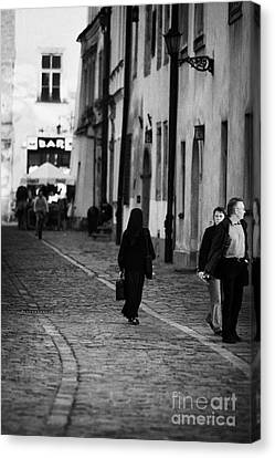 nun with briefcase walking up cobblestone street Kanonicza past tourists in old town krakow Canvas Print by Joe Fox