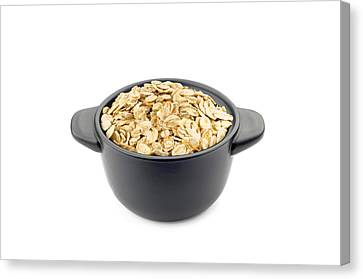 Oat Flakes In A Black Cup Canvas Print by Alain De Maximy