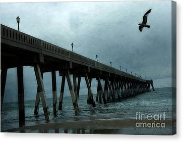 Flying Seagull Canvas Print - Oean Pier - Surreal Stormy Blue Pier Beach Ocean Fishing Pier With Seagull by Kathy Fornal