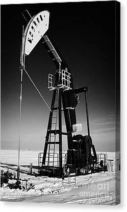 oil pumpjack in winter snow Forget Saskatchewan Canada Canvas Print by Joe Fox
