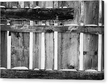 old patched up wooden fence using old bits of wood in snow Forget Canvas Print by Joe Fox