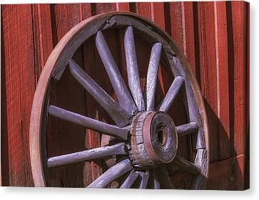 Old Wagon Wheel Leaning Against Barn Canvas Print