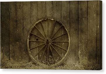 Old Wagon Wheel On Barn Wall Canvas Print by Dan Sproul