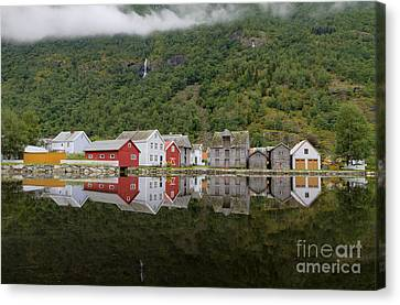 Old Wooden Houses Reflected In Water At Laerdalsoyri Norway Canvas Print by Bart De Rijk