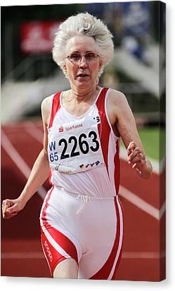 Older Female Athlete Runs To Camera Canvas Print by Alex Rotas