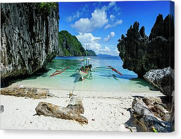Outrigger Boat On A Little White Beach Canvas Print by Michael Runkel