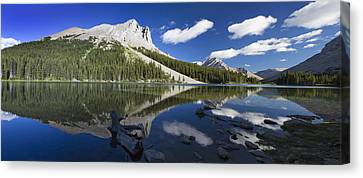 Panorama Of A Mountains Reflecting On A Canvas Print by Michael Interisano