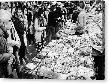 people buying chocolates on display inside the la boqueria market in Barcelona Catalonia Spain Canvas Print by Joe Fox