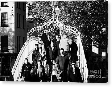 People Crossing The Hapenny Ha Penny Bridge Over The River Liffey In Dublin At A Busy Time Canvas Print by Joe Fox