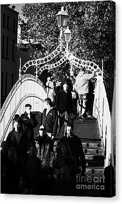 People Crossing The Hapenny Ha Penny Bridge Over The River Liffey In Dublin At A Busy Time Vertical Canvas Print by Joe Fox