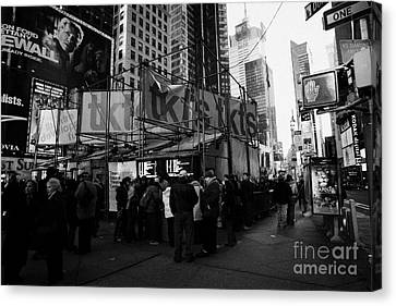 people customers queuing outside the tickets TKTS booth in times square new york city Canvas Print by Joe Fox
